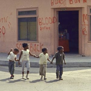 """Caption from LIFE. """"Children in Watts grow up with the signs of fear, desperation and hatred all around. The words painted last August on this little grocery store, telling rioters that it is owned by a Negro and urging them to burn something else, were left on the walls for months afterwards -- just in case."""""""