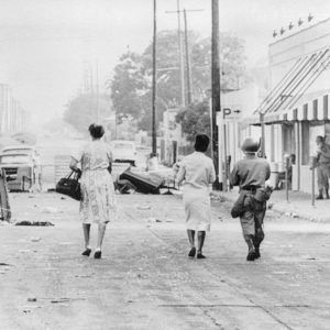 LOS ANGELES, CA--August 15, 1965--A rifle-carrying National Guardsman escorts two women through the debris-littered streets of Watts where rifle fire from snipers continued to harass Negroes and whites alike in Los Angeles' riot zone. The women were bound for Sunday church services. (AP Wirephoto.)